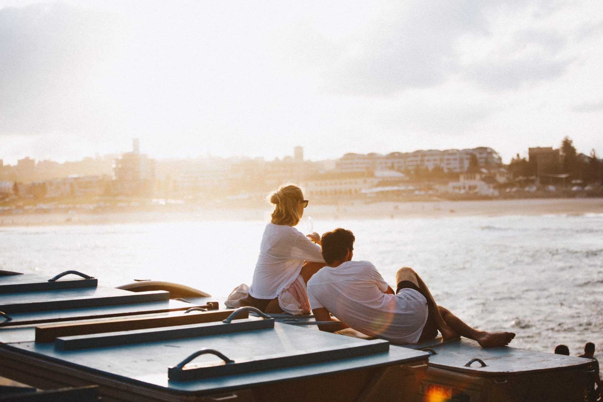 Couple sitting on shore watching the ocean